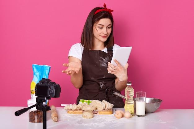 Baczna rozważna brunetka z czerwonym pałąkiem patrzeje ekran pastylki