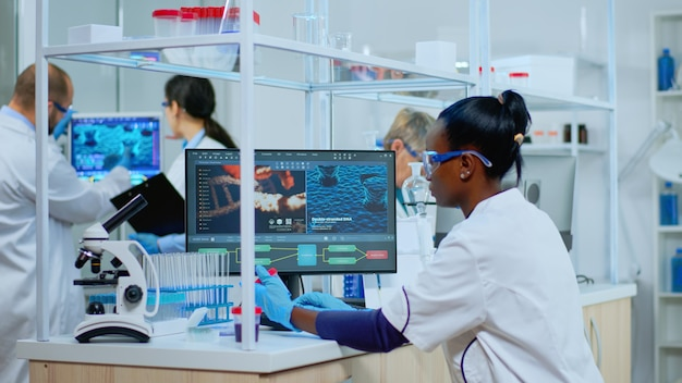 Badacz czarna kobieta prowadząca badania naukowe w wyposażonym laboratorium. wieloetniczny zespół badający ewolucję wirusa przy użyciu zaawansowanych technologii do badań naukowych nad opracowaniem leczenia przeciw covid19