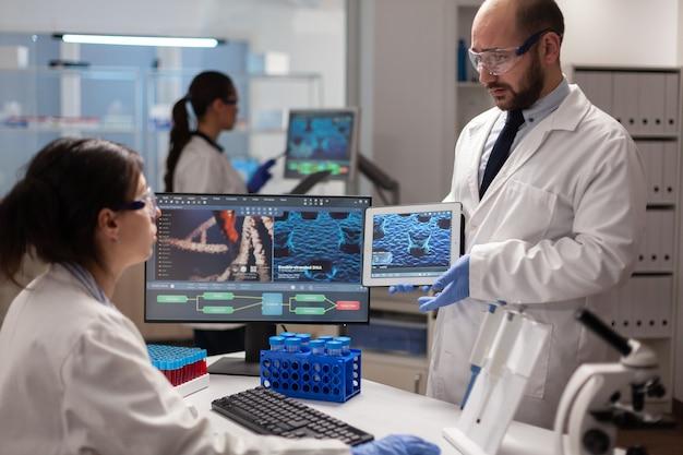 Badacz medyczny dyskutujący o ewolucji wirusa porównujący informacje dna z tabletu