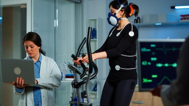 Badacz medyczny korzystający z laptopa podczas pomiaru wytrzymałości sportowca za pomocą czujników ciała, elektrod i maski mierzącej rytm serca