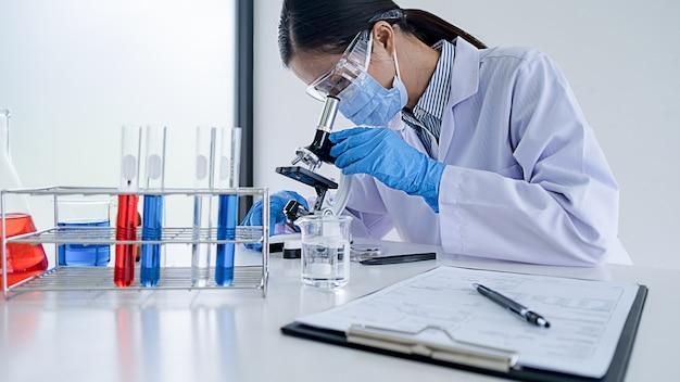 Badacz medyczny lub naukowy lub lekarz patrzy na probówkę z przezroczystym roztworem w laboratorium