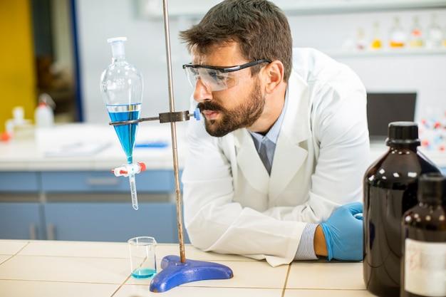 Badacz pracujący z niebieską cieczą przy rozdzielaczu w laboratorium