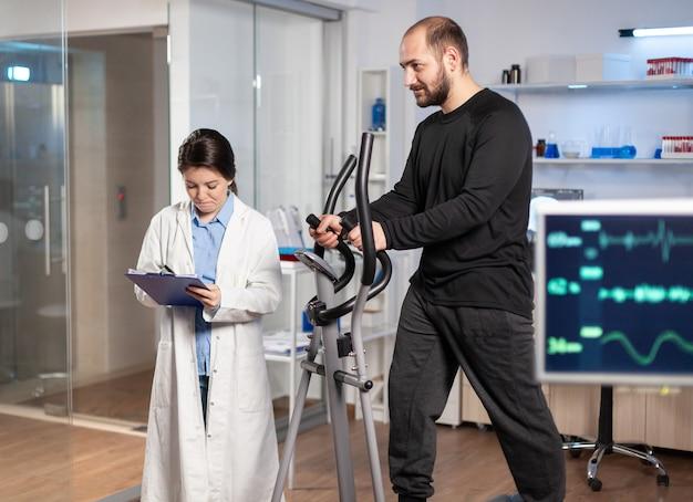 Badacz sportu w laboratorium robi notatki podczas biegania atleta muskularnego, badanie tętna. badanie wytrzymałości w profesjonalnym laboratorium biomechaniki.