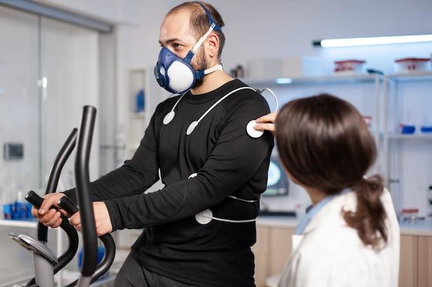 Badacz sportu w testowym badaniu wydolności sportowców, monitorowaniu, elektrodach na ciele, bieganiu kardio. analizator wytrzymałości ciała sensory sprzęt maszyna, sportowiec.
