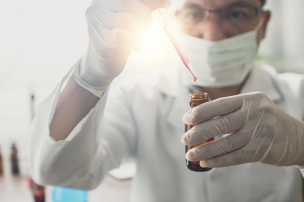 Badacz trzymający butelkę leku przeciwretrowirusowego