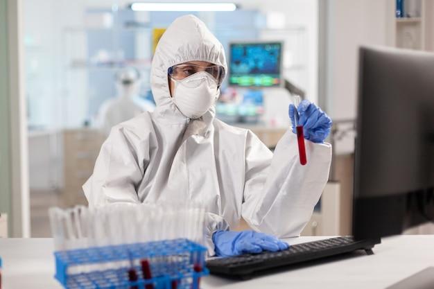 Badacz w kombinezonie trzymający probówki z próbkami krwi pisanymi na komputerze