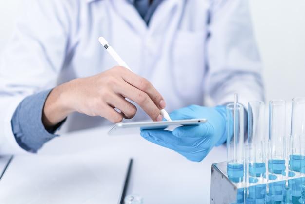 Badacz w laboratorium studia z chemikaliami i mikroskopami