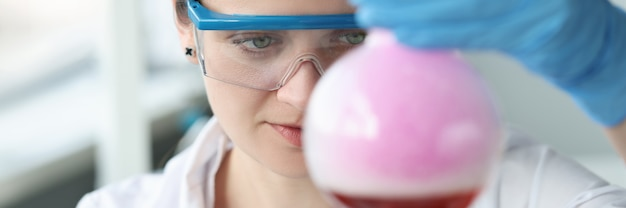 Badacz w okularach przeprowadza eksperyment chemiczny w składzie chemicznym kolby
