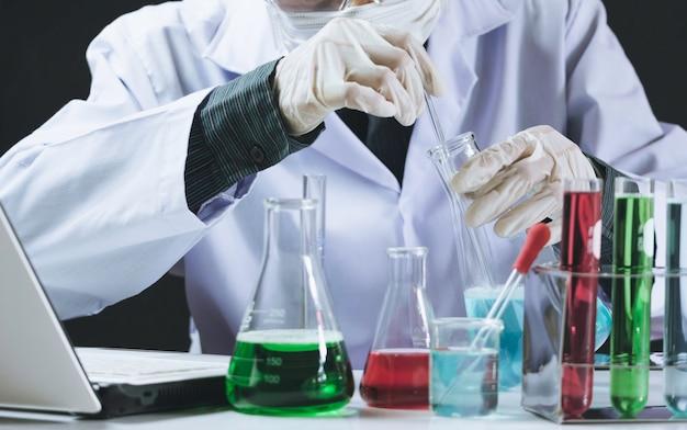 Badacz w szklanych laboratoryjnych probówkach chemicznych z płynem
