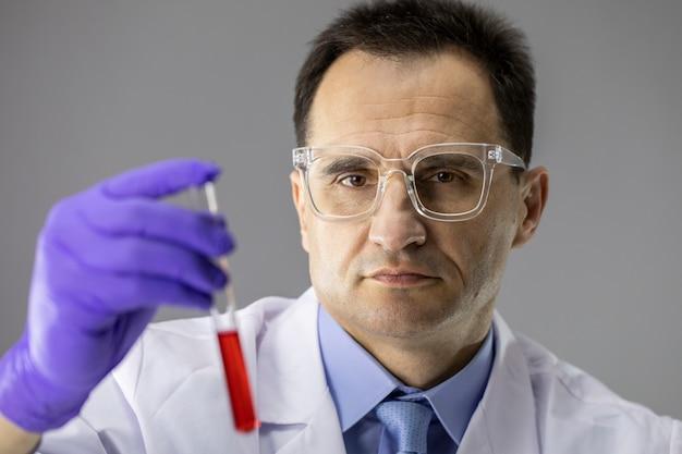 Badacz z bliska trzymając probówkę z czerwoną cieczą syntetyzującą nową szczepionkę
