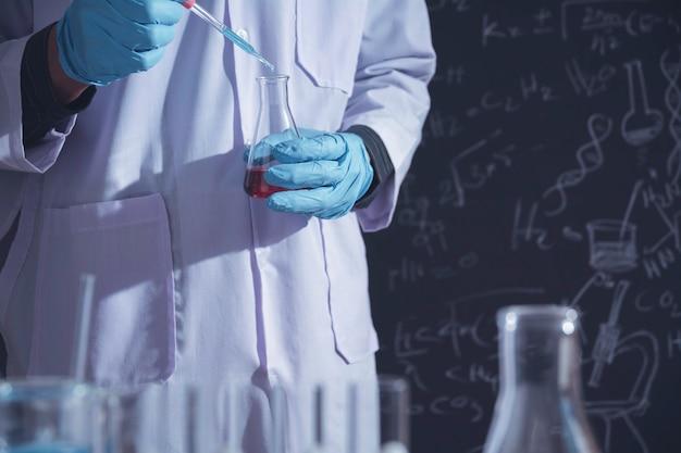 Badacz ze szklanymi laboratoryjnymi chemicznymi probówkami z płynem do badań analitycznych, medycznych, farmaceutycznych i naukowych.
