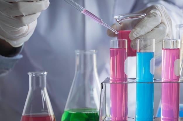 Badacz ze szklanymi laboratoryjnymi chemicznymi probówkami z płynem do koncepcji badań analitycznych, medycznych, farmaceutycznych i naukowych.