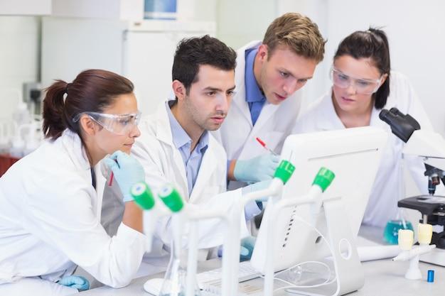 Badacze, patrząc na ekranie komputera w laboratorium