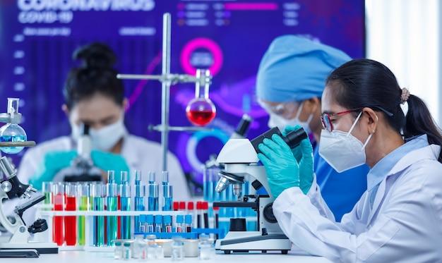 Badacze z grupy team skoncentrowali się na pracy z mikroskopem i sprzętem laboratoryjnym w sali laboratoryjnej wśród probówek i zlewek. koncepcja ciężkiej pracy naukowców w epidemii covid-19.