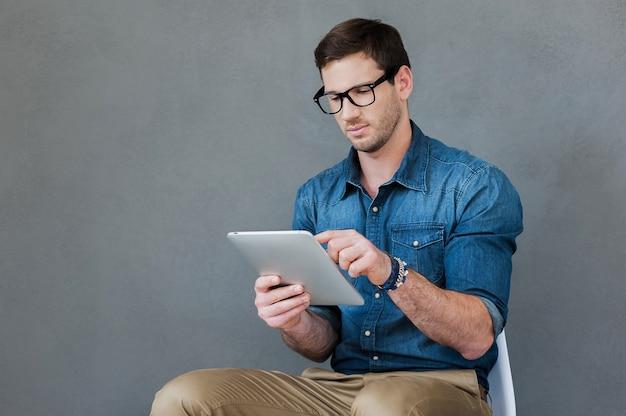 Badam jego nowy gadżet. przekonany, młody człowiek trzyma cyfrowy tablet