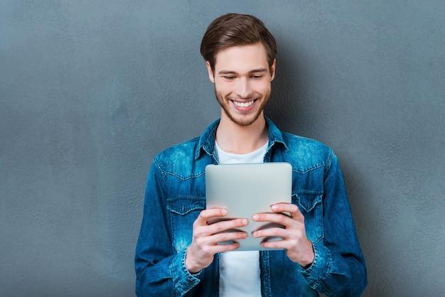 Badam jego nowy gadżet. szczęśliwy młody człowiek trzyma cyfrowy tablet i uśmiecha się