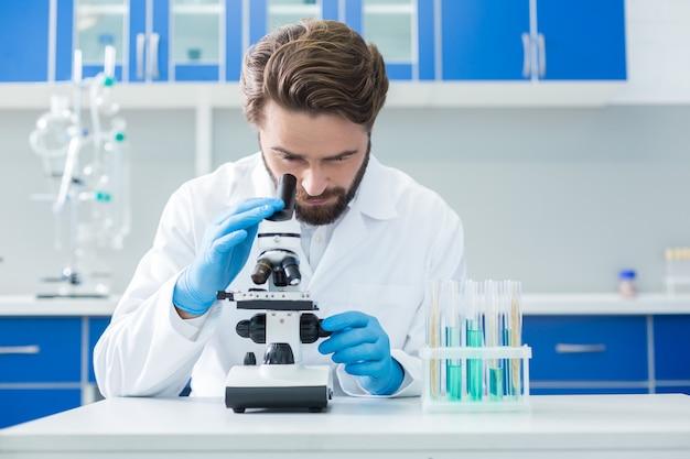 Badania biologiczne. mądry, miły, pewny siebie naukowiec patrzy przez mikroskop i testuje próbki podczas badań biologicznych