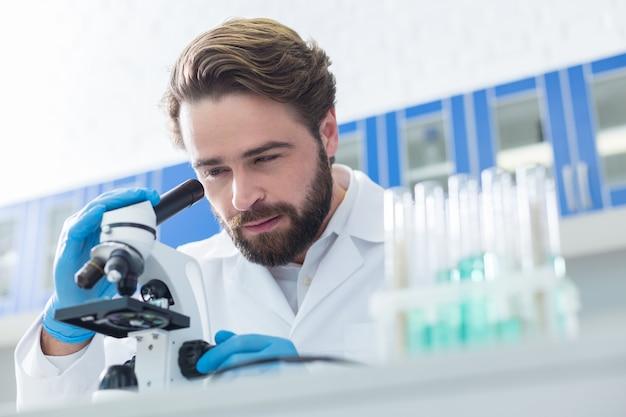 Badania chemiczne. profesjonalny inteligentny brodaty naukowiec siedzi przy stole i patrzy przez mikroskop podczas wykonywania profesjonalnych badań