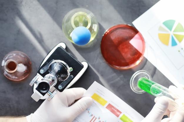 Badania laboratoryjne. testowanie narkotyków. eksperymenty chemiczne w laboratorium. pod mikroskopem różne probówki i zlewki na stole u lekarza.