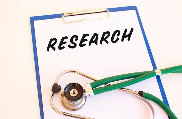 Badania - tekst w folderze medycznym z dokumentami i stetoskopem