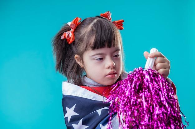 Badanie elementów dekoracji. poważna młoda dziewczyna z nieprawidłowościami chromosomowymi trzymająca fioletowy pompon podczas świątecznych dni