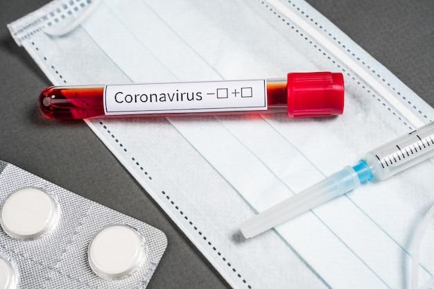 Badanie krwi na nowy koronawirus. probówka leży na szarym tle z maską ochronną i lekami.