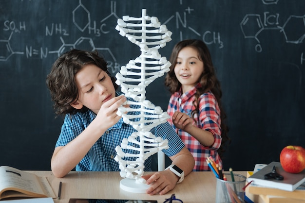 Badanie modyfikacji genomu. emotioanal obejmował zachwycone dzieci siedzące w szkole i cieszące się lekcjami chemii podczas pisania na tablicy i korzystania z modelu kodu genetycznego