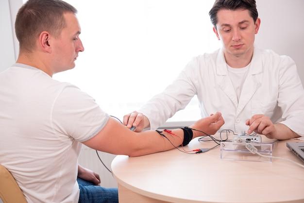 Badanie nerwów pacjenta za pomocą elektromiografii w centrum medycznym