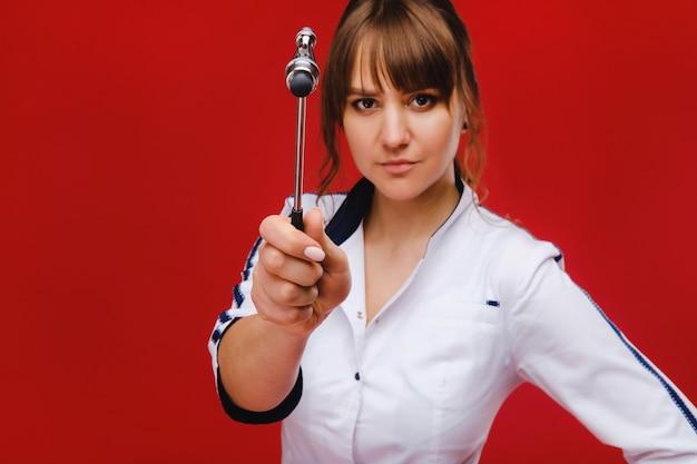 Badanie neurologiczne. neurolog testuje odruchy na pacjentce przy użyciu młotka. diagnostyka, opieka zdrowotna, usługi medyczne.