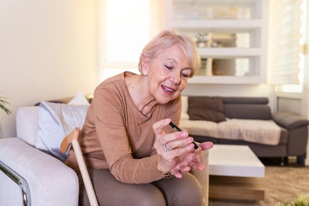 Badanie poziomu cukru we krwi w domu. sprawdzanie poziomu cukru we krwi w domu. sprawdzanie poziomu cukru we krwi. kobieta sprawdza poziom cukru we krwi glukometrem i paskiem testowym w domu