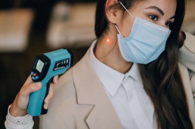 Badanie przesiewowe w kierunku koronawirusa. pracownik medyczny mierzący temperaturę ciała bezdotykowym termometrem ciała