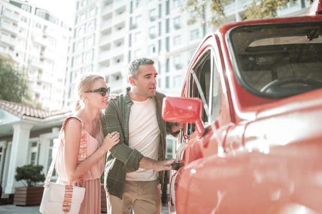 Badanie treści. skoncentrowany mąż i jego uśmiechnięta żona patrzą razem w okno swojego samochodu.