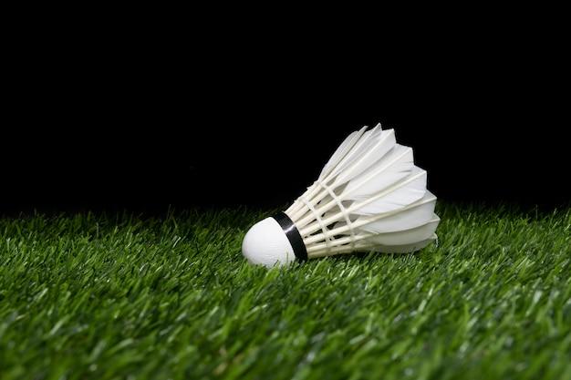 Badminton shuttlecock na trawie i czarnym tle