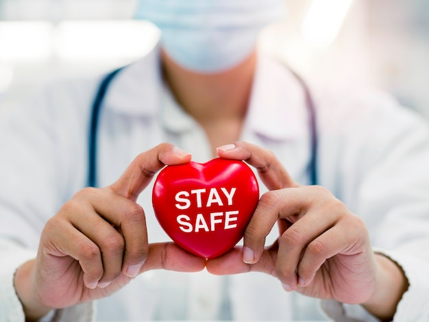 """Bądź bezpieczny, koncepcja opieki zdrowotnej i medycyny. zbliżenie na kobiece ręce lekarza trzymającego czerwone serce z napisem """"bądź bezpieczny"""", kampania na rzecz ludzi, aby pozostać w domu dla bezpieczeństwa przed pandemią koronawirusa."""