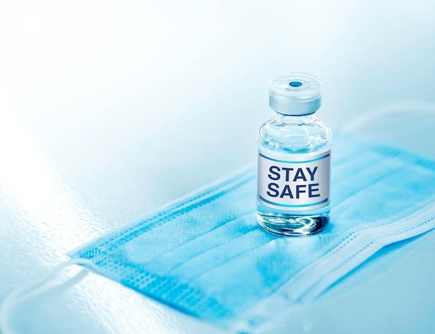 Bądź bezpieczny, słowo na etykietach na fiolce ze szczepionką na niebieskiej masce medycznej na stole
