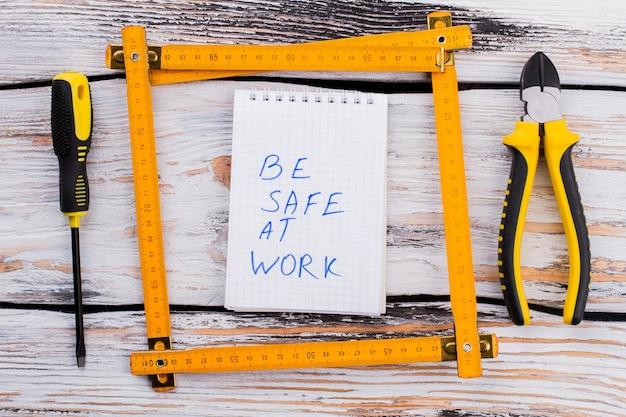 Bądź bezpieczny w pracy notatki w ramce linijki na białym drewnianym stole. wkrętak i szczypce, widok z góry na płasko.