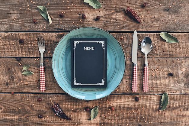 Bądź naszym gościem! ujęcie pod dużym kątem pustego talerza, widelca, łyżki, noża i zamkniętego menu