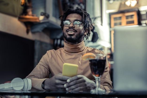 Bądź pozytywnie nastawiony. przystojny mężczyzna trzyma uśmiech na twarzy podczas przerwy w kawiarni