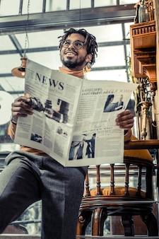 Bądź pozytywnie nastawiony. przystojny mężczyzna wyrażający pozytywne nastawienie podczas przeglądu prasy