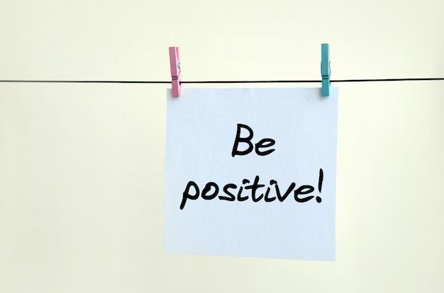 Bądź pozytywnie nastawiony! uwaga jest zapisana na białej naklejce, która wisi na sznurku na tle beżowej ściany