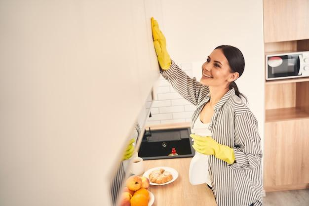 Bądź pozytywnie nastawiony. zachwycona młoda kobieta stojąca w półpozycji i czyszcząca meble z przyjemnością