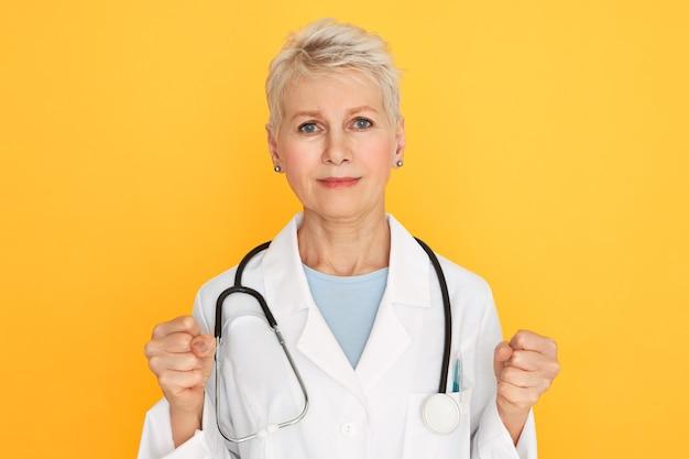 Badź silny. portret poważnej starszej lekarki w mundurze lekarskim zaciskającej pięści, zachęcającej pacjentów do walki z chorobą, jej spojrzenie pełne nadziei i determinacji.