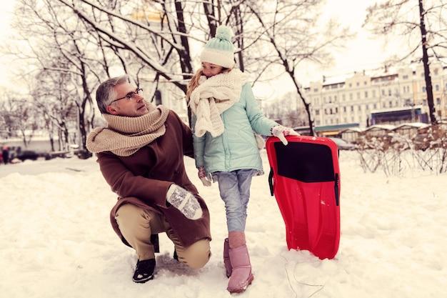 Bądź szczęśliwy. przystojny mężczyzna pieści swoją córkę, mając przyjazną rozmowę