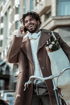 Bądź szczęśliwy. wesoły mężczyzna stojący w pobliżu roweru, rozmawiając z przyjacielem