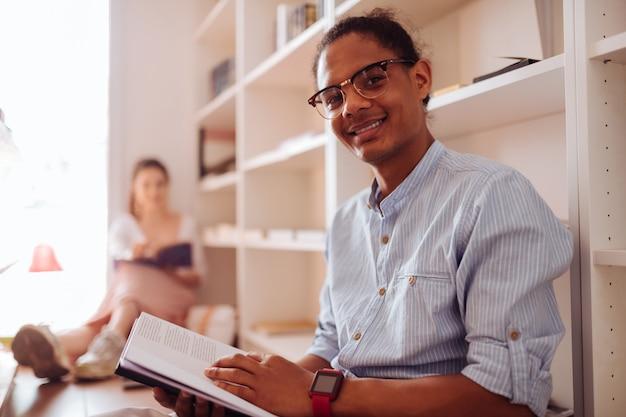 Bądź szczęśliwy. zachwycony młody mężczyzna z uśmiechem na twarzy trzymając książkę w obu rękach