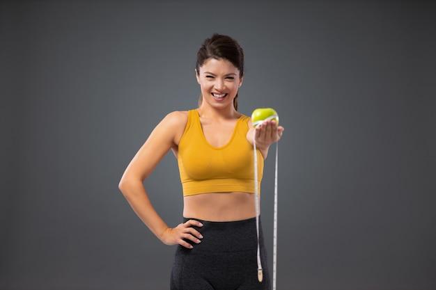Bądź szczupły i sprawny, wybierz zdrowy tryb życia. uśmiechnięta kobieta w stroju sportowym stoi przed szarą ścianą i trzyma w jednej ręce jabłko, aw drugiej taśmę obciążającą. zdrowe owoce i trening