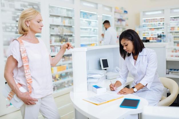 Bądź szybki. uważna brunetka aptekarz siedzi przy stole podczas pisania recepty