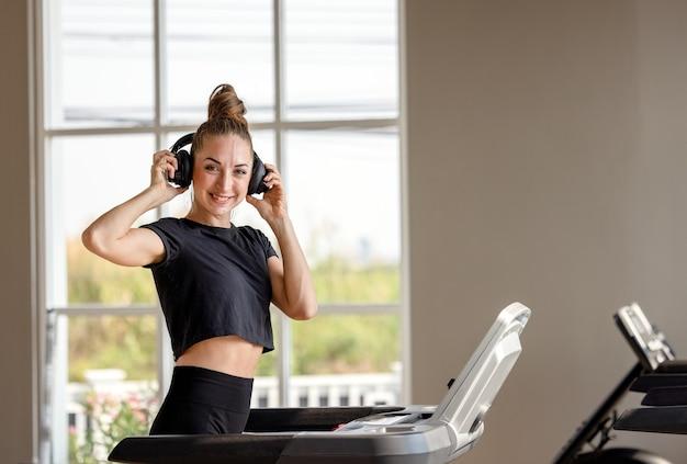 Bądź szybszy! widok z boku młodej i wesołej kobiety w odzieży sportowej biega na bieżni w siłowni i słuchania muzyki. trening cardio.