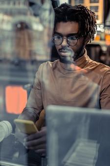 Bądź uważny. przystojny, międzynarodowy mężczyzna naciskając usta, wpatrując się w ekran swojego gadżetu