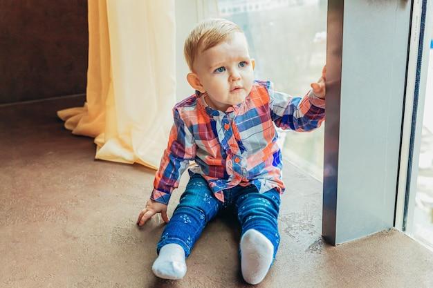 Bądź w domu bądź bezpieczny. mała śliczna słodka niemowlak mała dziewczynka siedzi blisko dużego okno w jaskrawym lekkim salonie w domu indoors. koncepcja czułości rodziny macierzyństwa dzieciństwa.